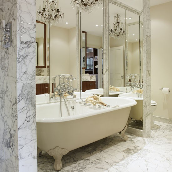 marble bathroom with large mirrors and chandelier